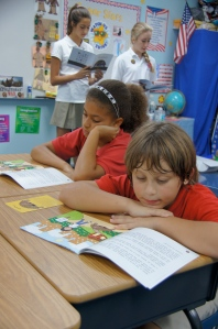 "Fifth grade students follow along as upper school students read ""Respect."""