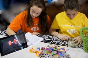Middle school students at Grandview Preparatory School participate in the school's annual Entrepreneur Fair, using an iPad to display styles of their bow creations.