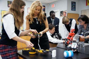 Head of school Jackie Westerfield learns the controls for a newly-designed robot in the middle school robotics class.