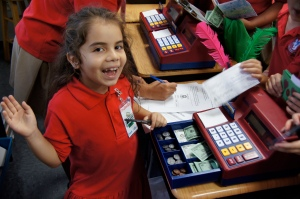 A second grade student serves as a banker during a Prideville day in November 2014.