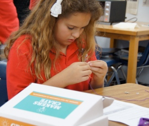 A student concentrates as she produces her product from the Maker's Crate.
