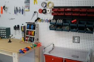 The interior of the Makerspace features an inventory room outfitted with tools and supplies and a work space with tables and work benches.